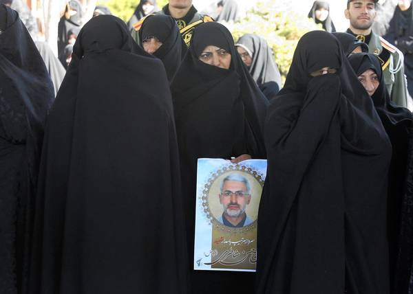Mourners attend the funeral of Iranian Gen. Hassan Shateri, shown in the poster at center, Thursday in Tehran.