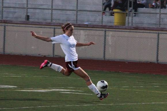 Katelyn Carballo of Laguna Beach powers a shot during Tuesday's CIF playoff game against Cerritos. The Breakers advanced in postseason by shutting out the visiting Dons, 5-0.