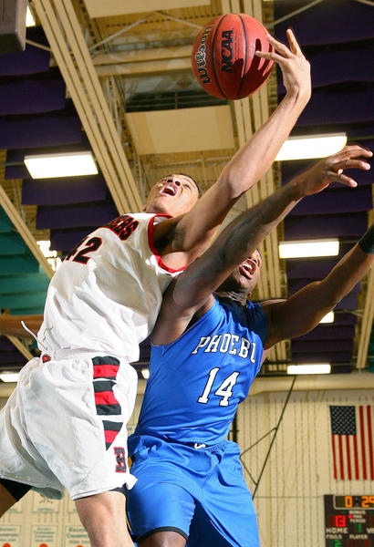 Tre Perry of Phoebus pulls in the offensive rebound from Attavius Matthews of Phoebus during the first half of their Peninsula District semi-final game Thursday at Woodside.