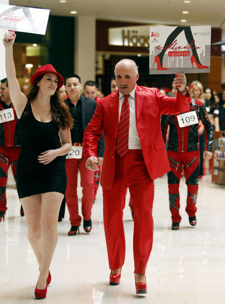 "American Heart Association's Tabitha Ellis, left, and Former L.A. Kings player Daryl Evans, right, lead a procession of men and women all wearing red shoes ""Go Red For Women Heels For Hearts"" event at the Glendale Galleria in Glendale on Thursday, February 14, 2013. Members of Mexican group Grupo Ondeando, are in the background wearing heels. Dozens of people participated in the walk around inside the mall.  The event was held to raise awareness of heart disease at this 3rd annual event."