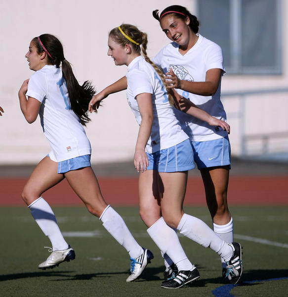 Crescenta Valley High's #17 Sierra Rhoads, center, is congratulated by #18 Katie Callister after Rhoads scores a goal during CIF SS Div. III first round girls' soccer playoff vs. San Luis Obispo High School at Crescenta Valley High School in La Crescenta on Thursday, February 14, 2013. CV won 1-0.