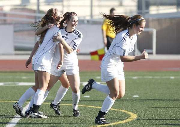 Corona del Mar High's Miranda Stiver, far left, gets hugged by Alana Hunter after scoring a goal.
