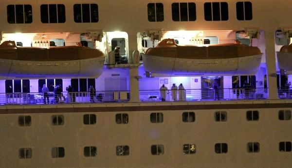Passengers stand along the railing as the Carnival Triumph cruise ship is towed towards the port of Mobile, Alabama, February 14, 2013. The 893-foot (272 meter) vessel, notorious for reports of raw sewage from overflowing toilets, has been without propulsion and running on emergency generator power since Sunday, when an engine room fire left it adrift in the Gulf of Mexico.