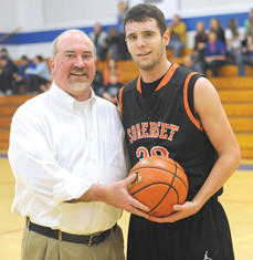 Head coach Scott Close presents the game ball to Somerset's Brent Barron after achieving his 1,000th career point Thursday night in Bedford.