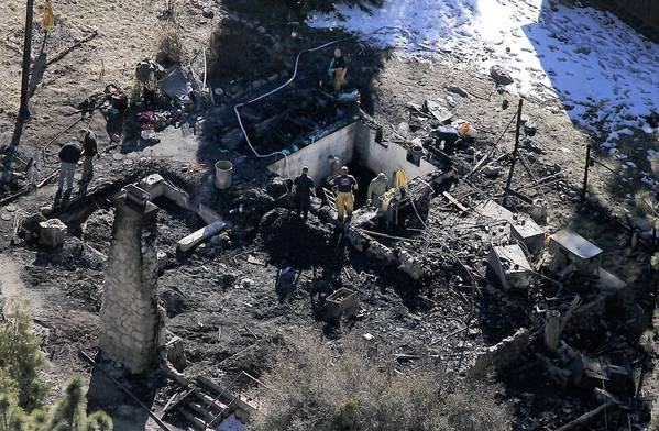 The remains of the cabin where Christopher Dorner and law enforcement officers traded fire are shown. The structure became engulfed in flames after canisters containing a powerful type of tear gas were deployed against the fugitive ex-cop inside.