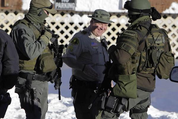 Jeremiah MacKay, center, and other San Bernardino County sheriff's deputies participate Saturday in the manhunt for Christopher Dorner in the Big Bear area.