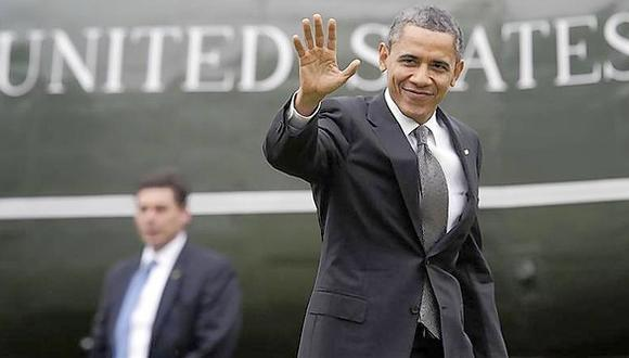 Obama waves to reporters as he returns from a daytrip in North Carolina, to the White House in Washington