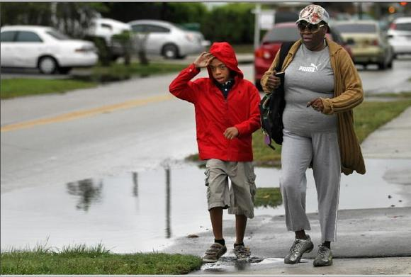 Frederica and Jayden Clark rush down NE 56th Street in Ft. Lauderdale on a soggy Friday morning, Feb. 15, 2013.