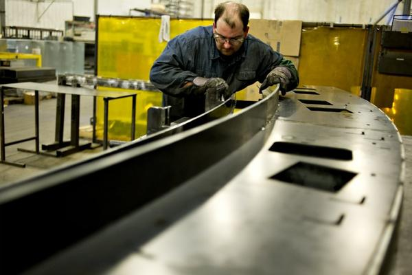 Corey DeMoss assembles a railing assembly for an escalator at the Giese Manufacturing Co. in Dubuque, Iowa.