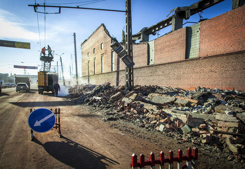 Workers repair a power line near the wall of a local zinc plant which was damaged by a shockwave from a meteorite in the Urals city of Chelyabinsk.