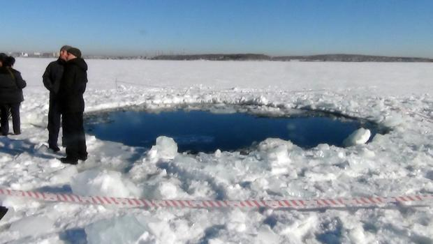 People stand near a 20-foot hole in the ice of a frozen lake, reportedly the site of a meteorite impact, in the Chelyabinsk region.