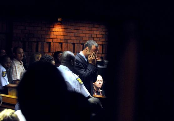 Oscar Pistorius buries his face in his hands during his appearance Friday in a Pretoria courtroom to face a charge of murder in the death of his girlfriend, model Reeva Steenkamp. The prosecution said it would argue the killing was premeditated murder, the most serious category of offense under South African law.