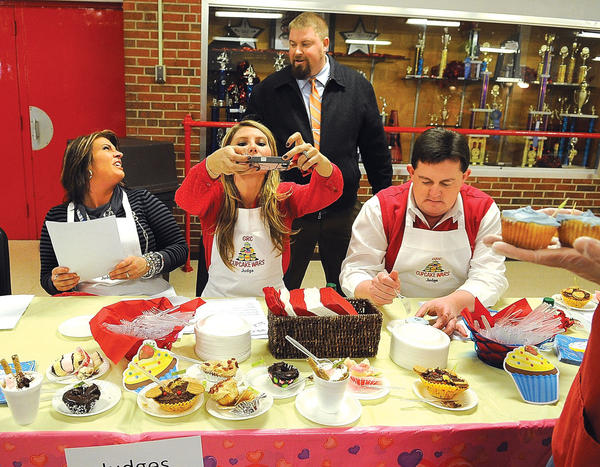 Celebrity judge Lauren Mink takes a photo of the cupcakes Thursday that she and fellow judges taste-tested during the George Rogers Clark High School Valentine¿s Day Cupcake Wars, top photo. Judging with Mink are GRC teacher Amanda Reffitt and Principal David Bowen. Watching is Phoenix Academy Principal Dustin Howard. There were 37 cupcake entries, three from the faculty and the rest from GRCHS and Phoenix Academy students. Student judge James Griffith tastes a cupcake with bacon as the topping, right photo. Judges, from left, cafeteria manager Tina Banks, Griffith, Reffitt, Mink and Bowen give a score for one of the cupcakes. First-place winners are Amanda Hurtz, Rachel Hardiman, Shelby Caudill and Willa Curry; second-place winners are Abby Houston and Courtney Thompson and winning third-place is Haley Strejan. Winning the best made-from-scratch category was Isabella Jones, and the winning the faculty category was Patricia Fraley. The event was a fundraiser for Special Olympics.