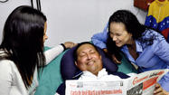 Venezuela released its first photos of President Hugo Chavez recovering from a December surgery on Friday, showing the ailing leader lying down with his head propped up on a pillow, two of his daughters at his sides.