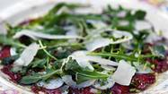 "According to my ""Grande Enciclopedia Illustrata della Gastronomia,"" carpaccio is the ""celebrated preparation based on raw beef sliced as finely as prosciutto di Parma and variously garnished,"" and was invented by Giuseppe Cipriani at Harry's Bar in Venice. A regular there, Contessa Amalia Nani Mocenigo (of Venice), was given a strict diet by her doctor. One of the few things she could eat was <em>carne cruda </em>— raw beef. To make her diet less monotonous, Cipriani presented her one day with a dish of finely sliced raw beef scribbled over with a mayonnaise spiked with mustard and a dash of Worcestershire. He named it ""carpaccio"" after the painter Vittore Carpaccio, whose paintings were showing in Venice at the time. Cipriani was particularly taken with his use of red."