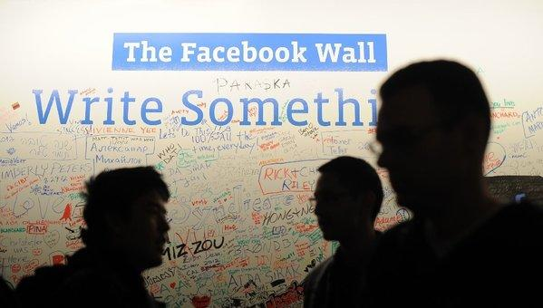 "Employees gather in front of a white board called ""The Facebook Wall"" at Facebook headquarters in Menlo Park, Calif."