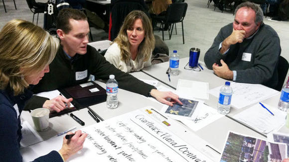 Janice Lampert (l) takes notes for her group as John Burt, Susie Marshall and Joe Duff discuss new uses for the courthouse lawn as a central park for a redesigned downtown Gaylord at a Feb. 7 workshop.