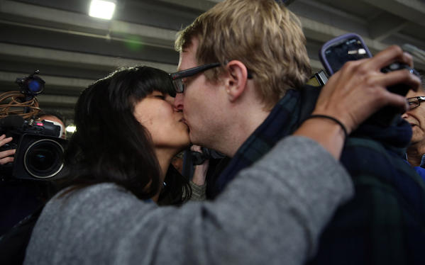 Sandeep Berry kisses her husband, Tom Berry, after arriving at O'Hare International Airport on Friday, morning. Berry was one of the passengers aboard the Carnival Triumph cruise ship.