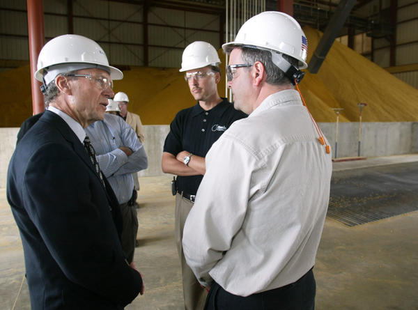 U.S. Senator Tom Daschle, left, talks with Jeff Broin, chief executive officer of Broin Companies, center and Kelly Kjelden, general manager of the James Valley Ethanol Plant, right, during a tour of the facility near Groton Tuesday. The trio are standing in the receiving building where corn is dropped off to be processed into ethanol. The mounds in the background are distillers grain, a bi-product of the ethanol making process that is used as a cattle feed supliment. photo by john davis taken 5/27/2003