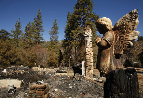 A ceramic angel stands watch over the charred debris at the cabin on Seven Oaks Road in Angelus Oaks where murder suspect and former cop Christopher Dorner died in a shootout this week with law enforcement.