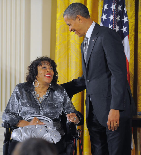 Constrained to a wheelchair since being struck by a car when she was 24 years old, medal recipient Janice Y. Jackson of Baltimore shares the stage with President Barack Obama, who leans close to her during the Presidential Citizens Medal ceremony at the White House.