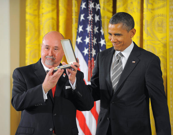 Michael Dorman holds his medal case while standing with President Barack Obama during the Presidential Citizens Medal ceremony at the White House.