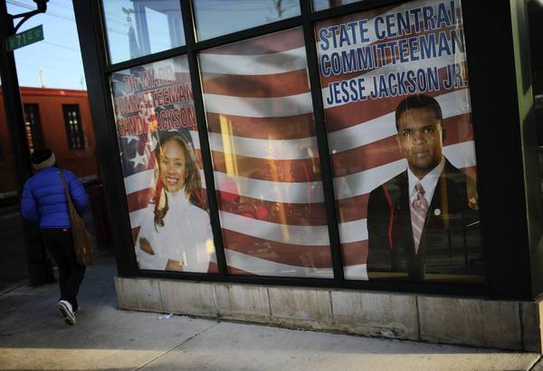 Jesse Jackson Jr. and his wife, Sandi Jackson are still pictured in the window of their former South Shore headquarters on the day they were both charged with violating federal law. Former U.S. Rep. Jesse Jackson Jr. was charged today with misusing campaign funds. His wife, former Ald. Sandi Jackson, was charged with one count of filing false tax returns.