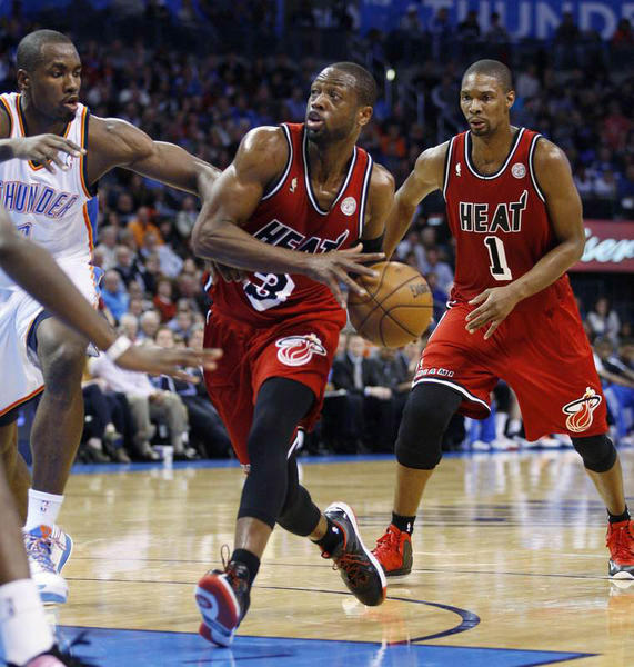Miami Heat guard Dwyane Wade (C) drives against Oklahoma City Thunder Serge Ibaka