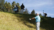 Graeme McDowell holds a club over his ball in the rough to help line up a drop on the fifth hole during the Northern Trust Open golf tournament at Riviera Country Club in Los Angeles