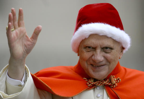 """Pope Benedict XVI, sporting a fur-trimmed hat in the rich red color of a Santa hat, waves to pilgrims upon his arrival in St. Peter's Square at the Vatican. The red hat with white fur trimming is known in Italian as the """"camauro."""""""