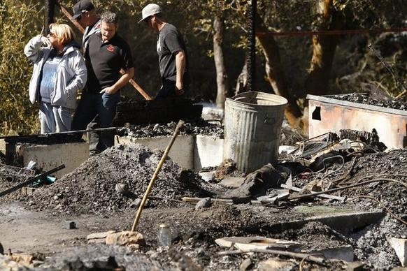Candy Martin and her sons look over what's left of their burned-down 90-year-old mountain home in Angelus Oaks, where fugitive ex-cop Christopher Dorner died in a shootout with law enforcement officials this week.