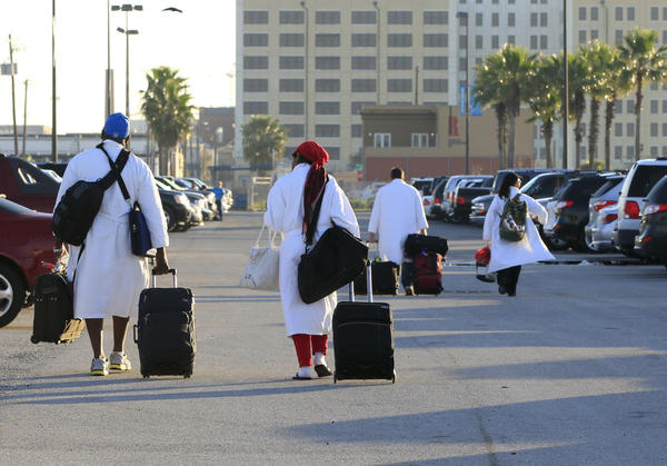 Passengers from the Carnival ship Triumph, wearing Carnival bathrobes, head to their cars after arriving in Galveston, Texas, from Mobile, Ala., on Friday. Galveston is the home port of the ill-fated ship, which lost power in an engine-room fire and was towed to Mobile.