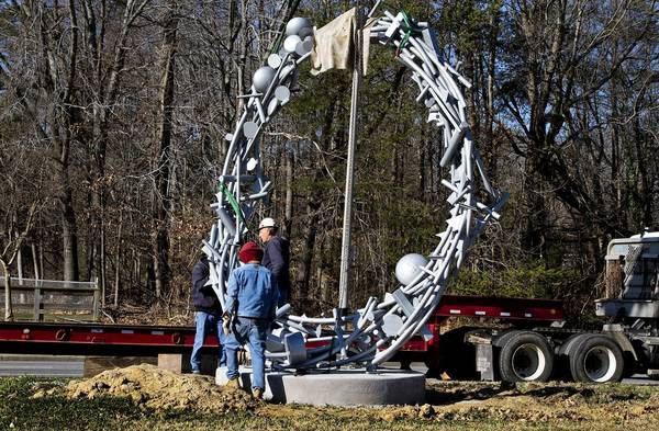 "Workmen place the bolts into the sculpture to hold ""Time"" in place on the second day of installation. ""Time"" was placed on Warwick Boulevard in front of Peninsula Memorial Park cemetery for the Newport News Public Art Foundation."