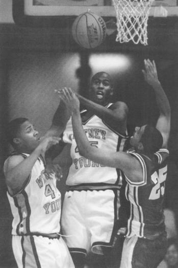 Young's Marquis Wright blocks Simeon Richard Lindsey's shot as Young's Corey Harris looks on at game at Chicago State in 1997.