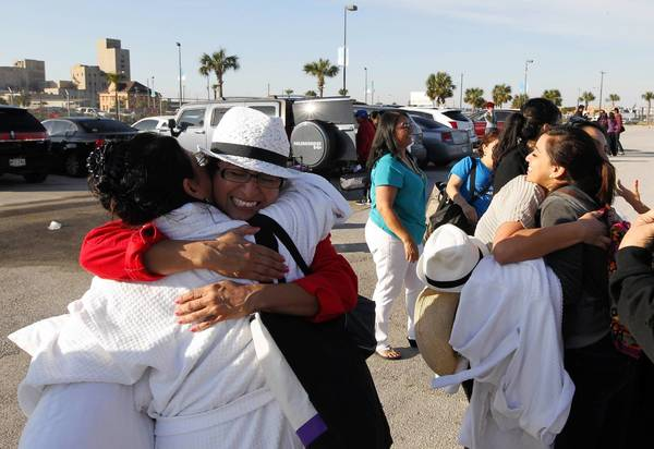 Cruise ship passengers reunite Friday in Galveston, Texas, after taking an eight-hour bus ride from Mobile, Ala., where the Carnival Triumph docked late Thursday night. Galveston is the home port of the ill-fated ship.