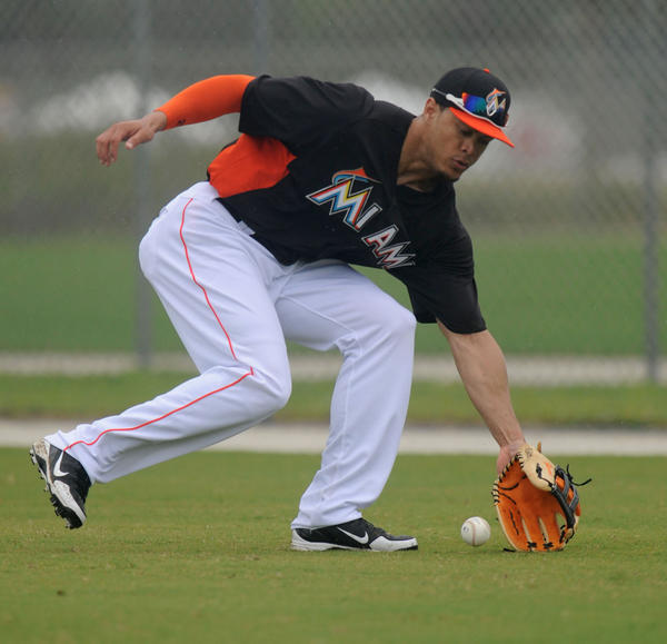 The Miami Marlins'  Giancarlo Stanton fields ground balls Friday afternoon as spring training gets underway in Jupiter.