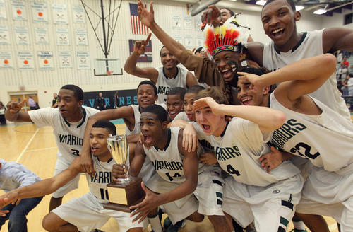 The Kecoughtan boys basketball team celebrates winning the Peninsula District tournament after beating Hampton 52-50 Friday at Woodside.