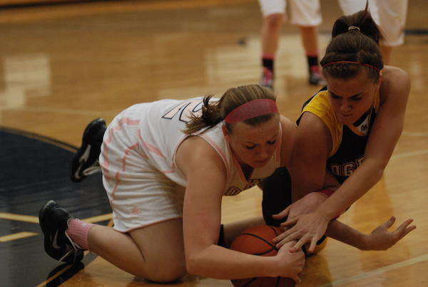 Petoskey senior guard/forward Kelsey Ance (left) dives for a loose ball with West Branch Ogemaw Heights Haley Izworski during Friday's Big North Conference contest at the Petoskey High School gym. Ance had a game-high 22 points as the Northmen defeated the Falcons, 53-25.