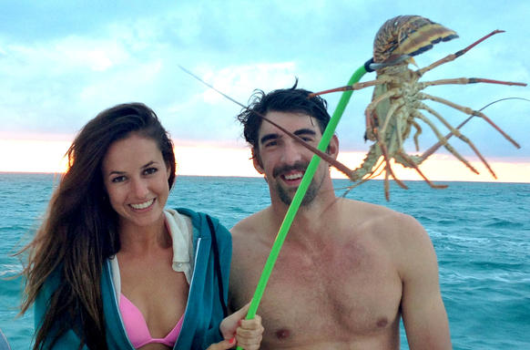 Sarah Herndon, with Michael Phelps, has the lobster right where she wants it.