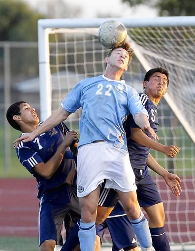 Corona del Mar High's Hunter Cullen (22) goes up strong for a header off a throw-in between California's Danny Garcia, left, and Valentin Cruz.