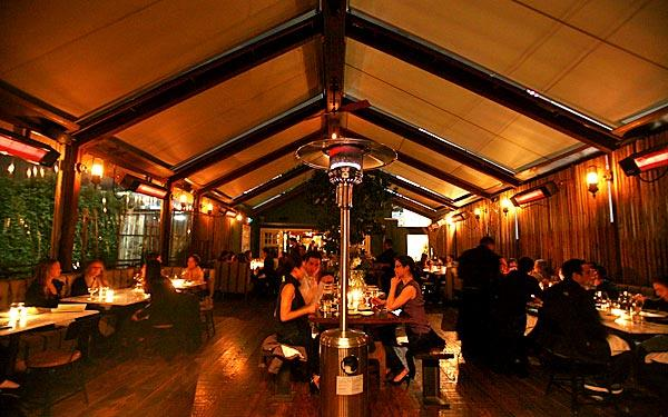 One of Eveleigh's dining rooms has a canvas roof, a communal table in the middle and open-air sides.