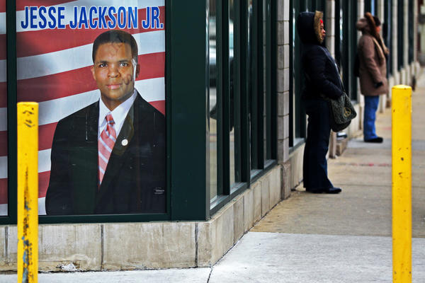 Riders wait for the number 71 bus as a window decal of former Rep. Jesse Jackson Jr. is shown in the window of his headquarters on Saturday in Chicago.