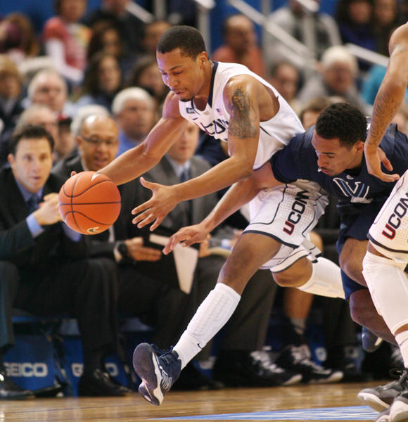 UConn guard Omar Calhoun chases down a loose ball ahead of Villanova guard Brendan Allen in the 1st half at the XL Center in Hartford Saturday.