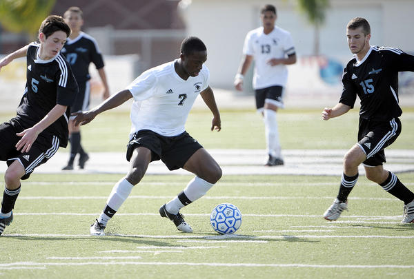 American Heritage's Jamar Champion-Hinds dribbles the ball through the middle of the Ponte Vedra defense during the first half of their state finals game.