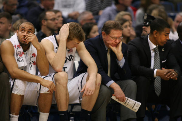 UConn players R.J. Evans, and Neils Giffey with coaches George Blaney and Kevin Ollie absorb UConn's loss to Villanova 61-70 at the XL Center in Hartford Saturday.