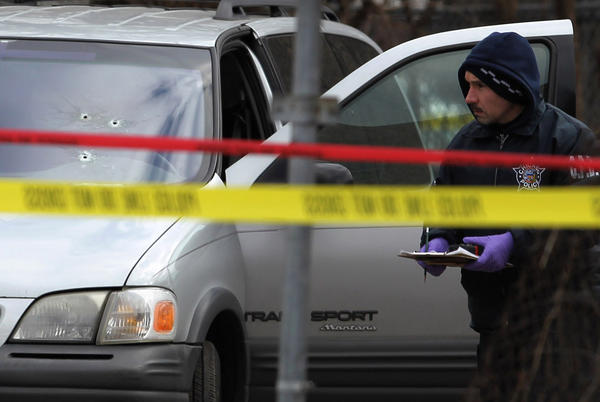 A Chicago police investigator surveys the scene of police-involved shooting near Springfield and Chicago Avenues.