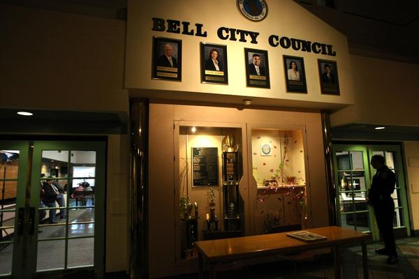 A Bell police officer looks in on a Bell City Council meeting from the lobby of the Bell Community Center. Portraits of current city officials hang over the entrance to the center.