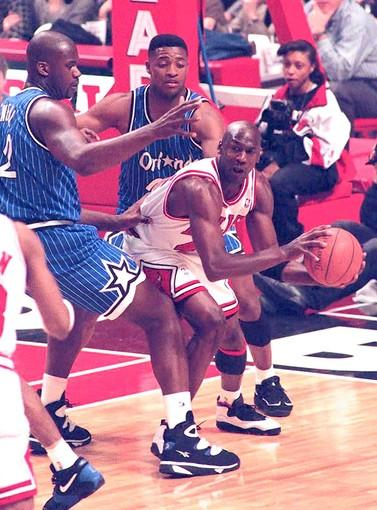 Michael Jordan of the Chicago Bulls, center, tries to get rid of the ball under pressure by Magic center Shaquille O'Neal, left, and guard Nick Anderson in 1995.