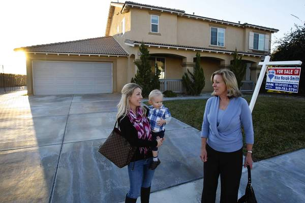 Shannon Bridgewater, holding her son, Brayden, confers with agent Carey Chenoski after checking out a home in the Yucaipa area last week.