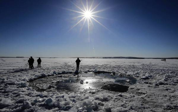 "A large piece of the space rock is believed to have punched this hole in Chebarkul Lake, west of Chelyabinsk, Russia. Divers' initial search of the lake did not turn up any remnants of the object, which NASA called a ""tiny asteroid."""